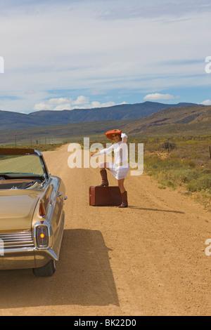 Woman hitching on desert road - Stock Photo