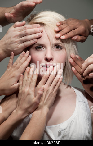 Woman being touched by many hands - Stock Photo