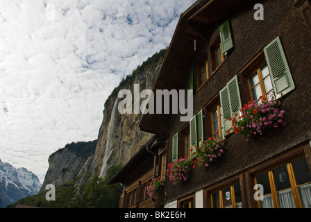 Waterfall falling into the Lauterbrunnen valley on a summer day with swiss chalet in foreground - Stock Photo