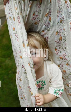 Little girl hiding behind curtains - Stock Photo