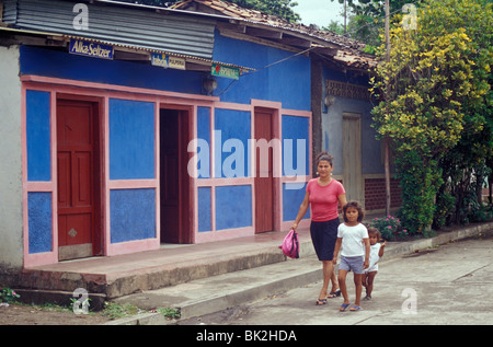 Woman and two young children walking down a street in Moyogalpa, Isla de Ometepe or Ometepe Island, Nicaragua - Stock Photo