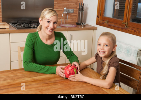 Mother and daughter hold a piggy bank - Stock Photo