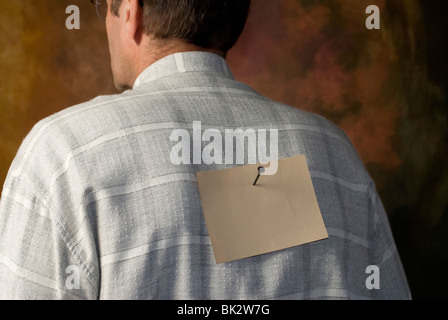 note nailed to man's back - Stock Photo