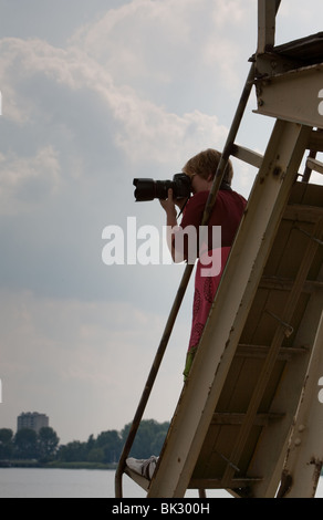 Female photographer shooting with a dslr camera standing on a construction - Stock Photo