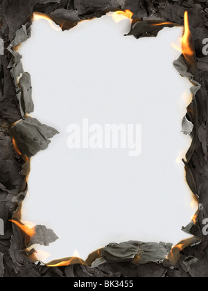 Burning paper ashes revealing blank white background making a frame - Stock Photo