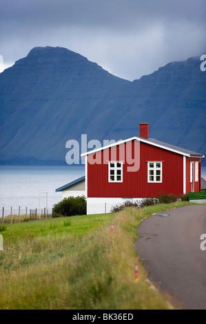 Houses at Hellur, small village near Oyndarfjordur, cliffs of Kalsoy Island in background, Eysturoy, Faroe Islands - Stock Photo