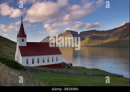 Church built in 1920 at Husar, Kalsoyarfjordur and Kunoy hills in the distance, Kalsoy, Nordoyar, Faroe Islands - Stock Photo