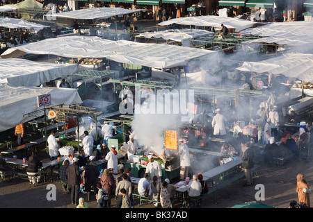 High view of food stalls, cooking and people in Djemma el Fna square in early evening in the Medina, Marrakech, - Stock Photo