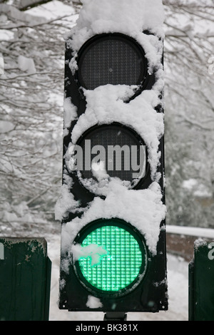Snow covered traffic lights showing green. - Stock Photo