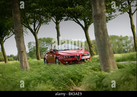 Alfa Romeo Spider driving along a French country road - Stock Photo