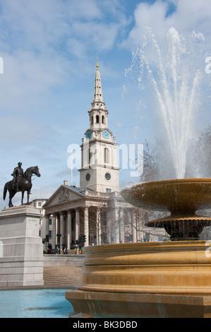 Trafalgar square fountain with St Martin's in the Field - Stock Photo