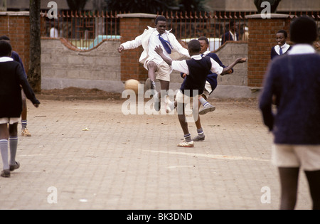 Kenyan school children in uniforms playing soccer, Nairobi - Stock Photo
