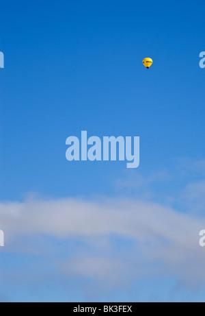 Tiny yellow hot air balloon airborne at blue sky - Stock Photo