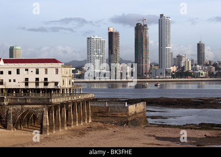 Ruined building in Casco Viejo at low tide , Paitilla skyscrapers in background , Panama City , Panama - Stock Photo