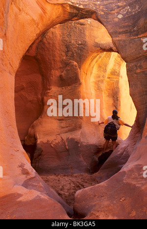 A woman admires the warm light in Peekaboo Gulch in the Escalante Canyons of Grand Staircase Escalante National - Stock Photo
