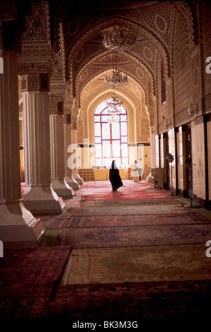 Interior of a mosque showing a hallway with carpets and chandeliers in Baghdad, Iraq - Stock Photo