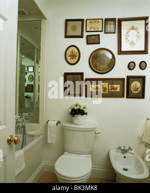 Collection Of Old Framed Pictures Above Toilet And Bidet In Small