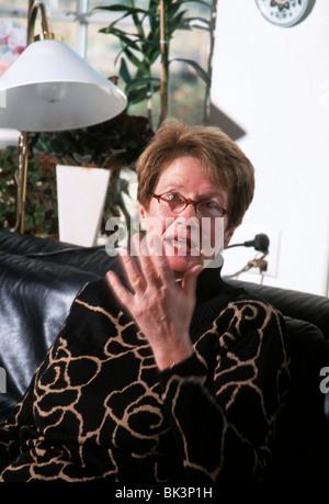 Rage elderly woman sit on sofa - Stock Photo