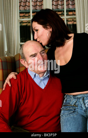 Young woman hugging with older man give him kiss on the head. - Stock Photo