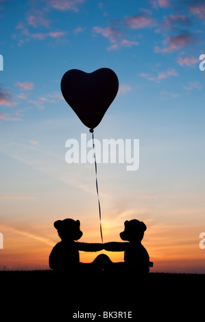 Two teddy bears holding a heart shape helium balloon at sunrise. Still life silhouette - Stock Photo