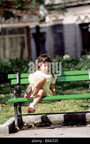 Young girl on a park bench, Cuba - Stock Photo