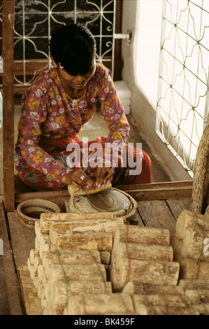 Thanaka cream being made by grinding bark wood or roots of a thanaka tree with a small amount water on a circular - Stock Photo