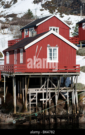 Traditional red wooden Rorbu fishermen`s huts in village of Å on Moskenesoya Island in Lofoten Islands in Norway - Stock Photo