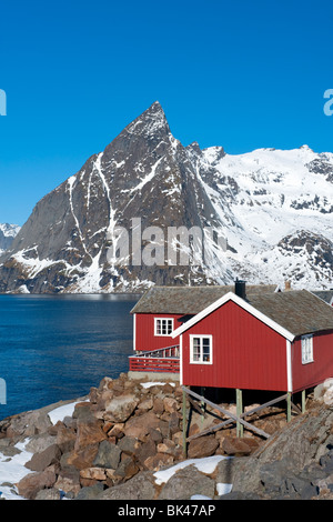 Traditional red wooden Rorbu fishermen`s huts in village of Hamnoy on Moskenesoya Island in Lofoten Islands in Norway - Stock Photo