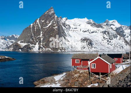 Traditional red wooden Rorbu fishermen`s huts in village of Hamnoy on Moskenesoya Island in Lofoten Islands in Norway - Stock Photo