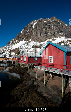 Traditional red wooden fishermen`s Rorbu huts by sea in Tind village in Lofoten Islands in Norway - Stock Photo