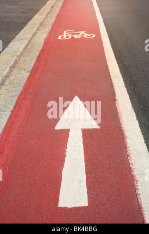 Bright Red Painted Cycle Path with White Cycle Symbol and One Way Direction Arrow - Stock Photo