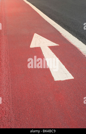 White Straight Ahead Direction Arrow Painted on a Bright Red Road Surface - Stock Photo
