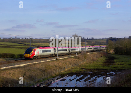 A Virgin Pendolino passes through Barby Nortoft (Nr Rugby) with a London Euston - Preston service on 02/03/2010. - Stock Photo