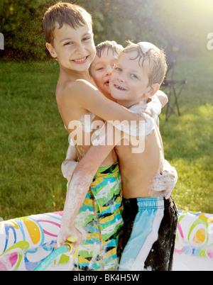 Brothers hugging in kiddie pool - Stock Photo