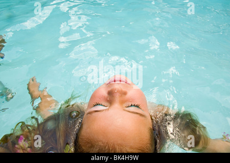 Young girl relaxing in swimming pool - Stock Photo