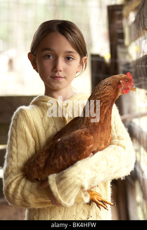 Girl with a big chicken in the chicken coup - Stock Photo