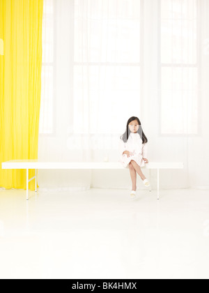Girl in white sitting in white room - Stock Photo