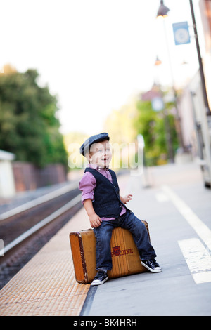 Young traveller sitting on suitcase - Stock Photo