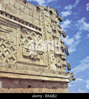 Architecture detail showing a relief sculpture of a human headed bird & a mask column at Nunnery Quadrangle in Uxmal - Stock Photo