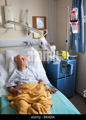 Patient in hospital bed watching television on swing arm while undergoing blood transfusion Wales UK - Stock Photo