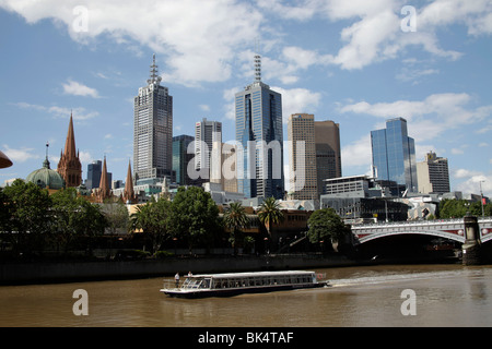 boat on Yarra River and the Melbourne Skyline with Flinders Street Station and the towers of St Paul's Cathedral, - Stock Photo