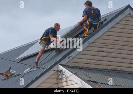 Workmen installing solar panels on roof in Hobart Tasmania Australia - Stock Photo