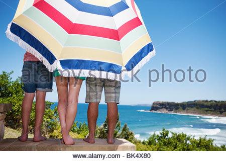 Friends under beach umbrella on patio overlooking ocean - Stock Photo
