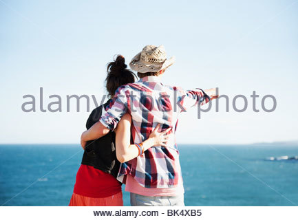 Couple hugging and pointing towards ocean - Stock Photo