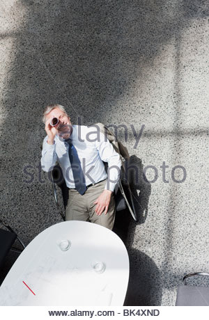 Businessman looking up through rolled up paperwork - Stock Photo