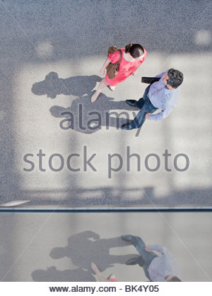 Businessman and businesswoman talking on sidewalk - Stock Photo
