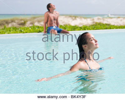 Woman standing with arms outstretched and eyes closed in swimming pool - Stock Photo