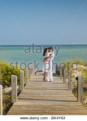 Couple hugging on ocean boardwalk - Stock Photo