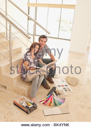 Couple reviewing carpet samples on stair in empty house - Stock Photo