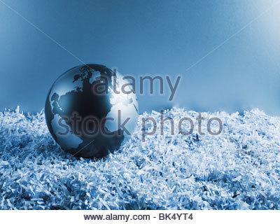 Metal globe on shredded paper - Stock Photo
